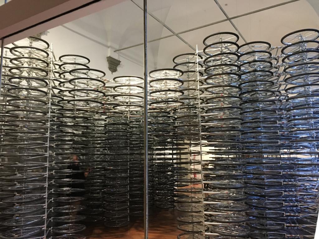 """L'installazione """"Stacked"""", composta da ben 950 biciclette, indica il mezzo di trasporto che è parte integrante della cultura cinese. In questa realizzazione Ai Weiwei vuole sottolineare due aspetti: il problema dei trasporti, molto sentito in Cina, e del suo impatto sull'ambiente, ma anche la libertà di movimento. Stacked, scollegandoci dal loro significato, allude ad un arco trionfale il quale ci introduce nella mostra."""